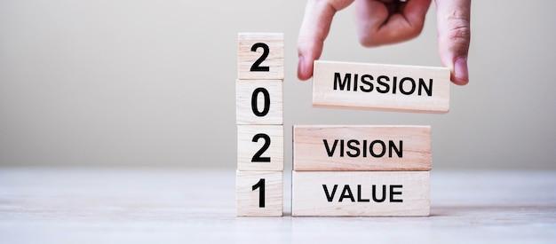 Zakenmanhand met houten kubus met tekst 2021 Premium Foto