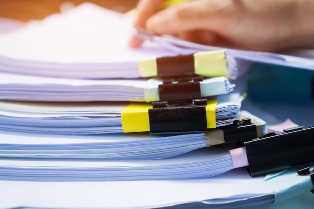 Zakenmanhanden die in stapels document dossiers werken voor het zoeken van controlerend onvolledig document Premium Foto