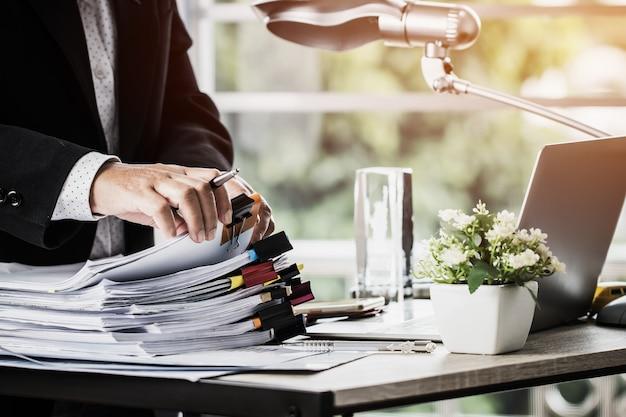 Zakenmanhanden die pen houden voor het werken in stapels van document dossiers Premium Foto