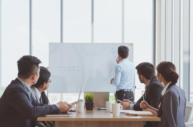 Zakenmanleider die op de whiteboard huidige bedrijfs marketing grafiek schrijven terwijl het ontmoeten van collega's in bureau. commerciële teamvergaderingspresentatie, conferentie plannings bedrijfsconcept Premium Foto