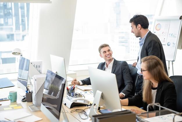 Zakenmansupervisor die met team in het bureau spreken Premium Foto