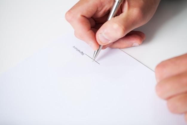 Zakenmanzitting bij bureau die contract ondertekenen Premium Foto