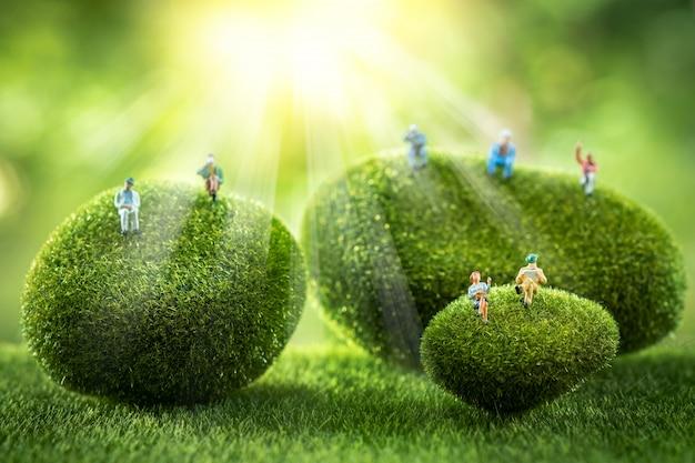 Zakenmensen zitten op een groene mos steen. Premium Foto