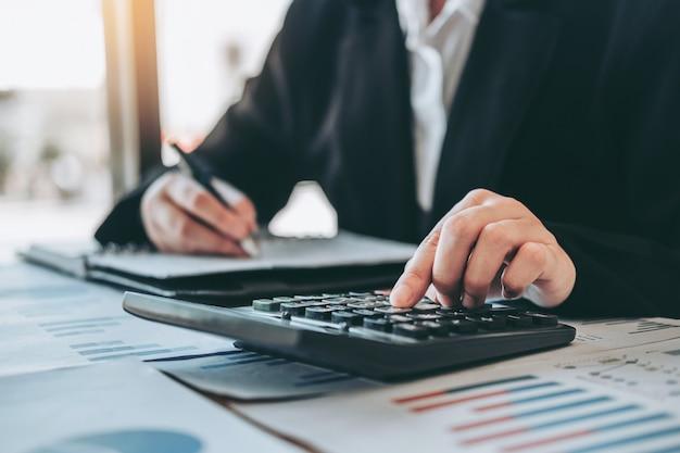 Zakenvrouw accounting financiële investering op rekenmachine kosten economische zaken en markt Premium Foto