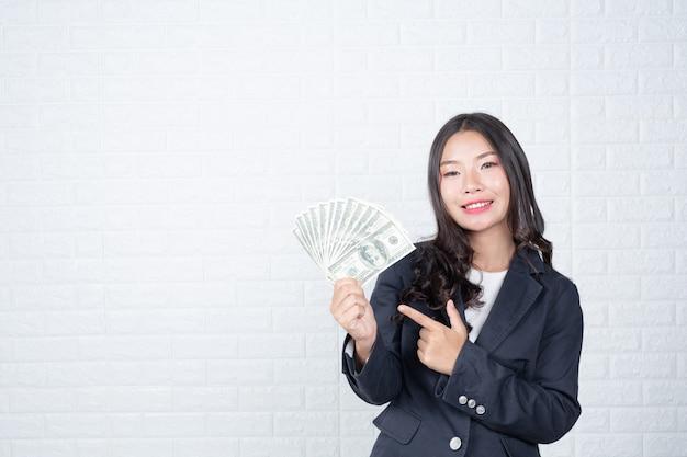 Zakenvrouw bankbiljet, contant geld afzonderlijk, witte bakstenen muur gemaakt gebaren met gebarentaal. Gratis Foto