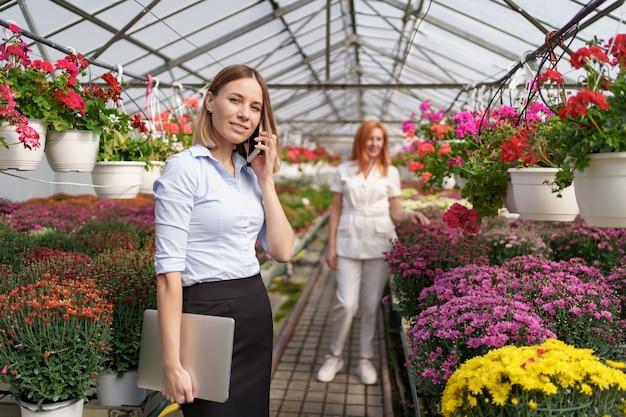 Zakenvrouw bespreken aan de telefoon een voorstel. ze heeft een laptop in een kas met bloemen. Gratis Foto
