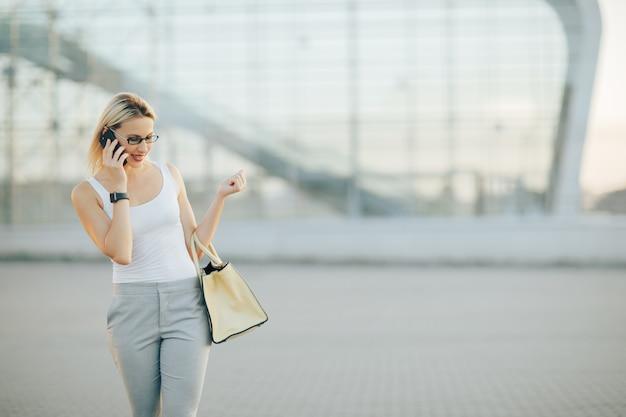 Zakenvrouw draagt een zonnebril in grijze broek spreekt telefonisch Premium Foto