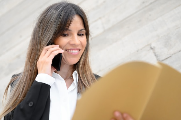 Zakenvrouw glimlachen, documenten in haar handen houden. hoge kwaliteit foto Premium Foto