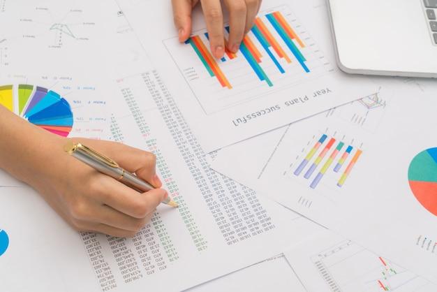 Zakenvrouw hand met financiële grafieken en laptop op de ta Gratis Foto