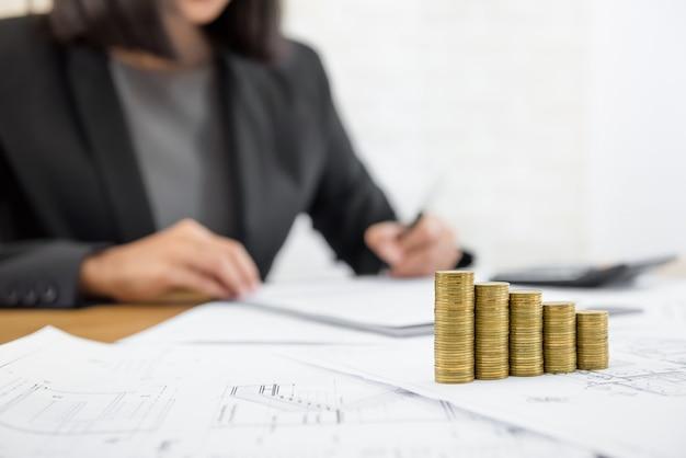 Zakenvrouw herziening document met geld en blauwdrukken op de tafel Premium Foto