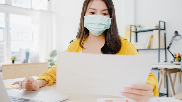 Zakenvrouw in azië die medisch gezichtsmasker draagt voor sociale afstand in een nieuwe normale situatie voor viruspreventie tijdens het gebruik van de laptop op het werk op kantoor. levensstijl na coronavirus. Gratis Foto