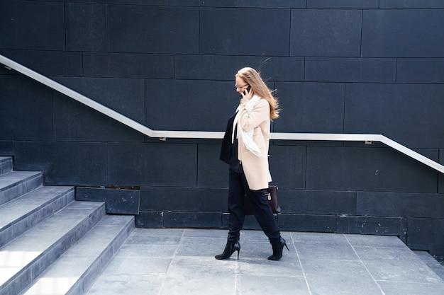 Zakenvrouw in een jas met een tas in haar handen gaat de trap op naar het gebouw. het concept van carrière en zaken Gratis Foto