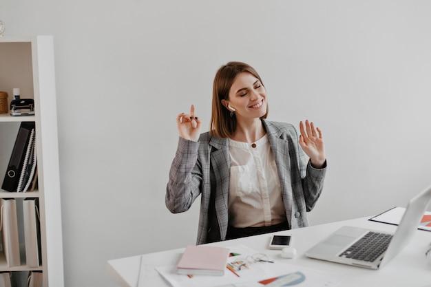 Zakenvrouw in grijze jas genieten van muziek zittend op de werkplek in wit kantoor. Gratis Foto