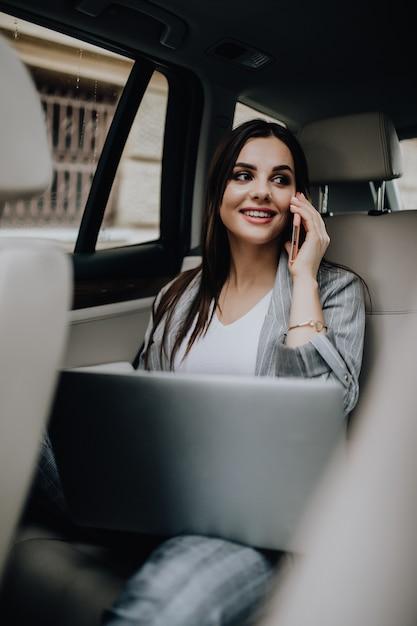 Zakenvrouw in haar auto met behulp van een laptop en een mobiele telefoon Gratis Foto