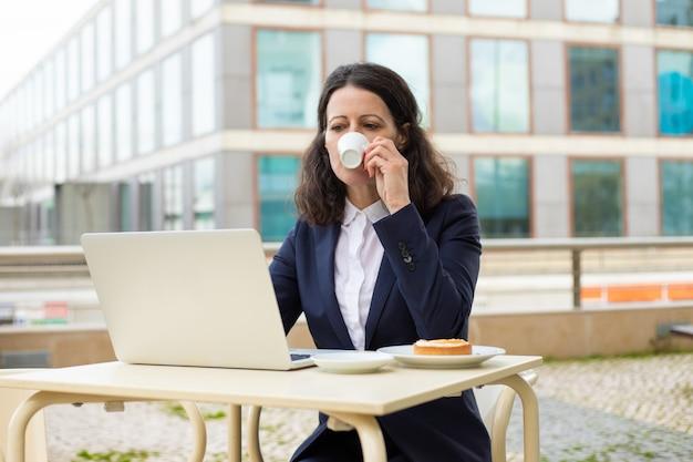 Zakenvrouw koffie drinken en laptop gebruikt Gratis Foto