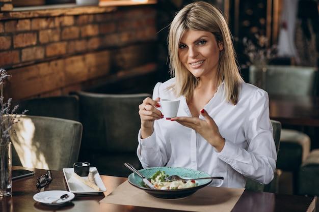 Zakenvrouw lunchen in een café Gratis Foto