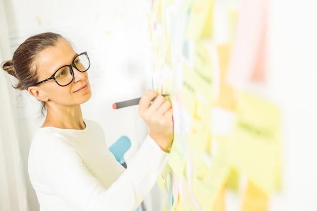 Zakenvrouw maakt een notitie op een papieren sticker Premium Foto