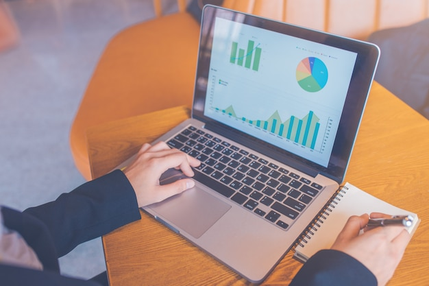 Zakenvrouw met behulp van een laptop op een houten bureau, en ze maakt aantekeningen op papier met een zwarte pen op kantoor, computer toont de analyse van de werkgrafiek, Premium Foto