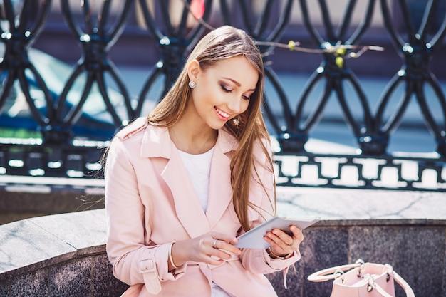 Zakenvrouw op pauze in het park. jonge professionele bedrijfsvrouw die tabletcomputer met behulp van openlucht. kaukasisch vrouwelijk model. Premium Foto