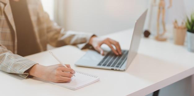 Zakenvrouw typen op laptop en schrijven op laptop Premium Foto