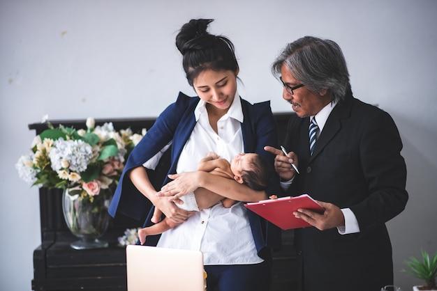Zakenvrouw werken vanuit huis, baby meisje te houden Premium Foto