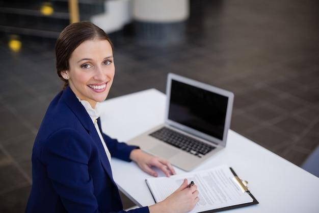 Zakenvrouw zit aan bureau met klembord en laptop Premium Foto