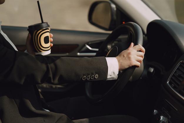 Zakenvrouw zit in een auto en drinkt een kopje koffie Gratis Foto