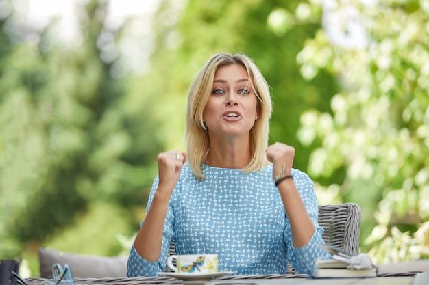 Zakenvrouw zit in spanning met koffie aan een tafel op een zomerterras. copyspace, groen. Premium Foto