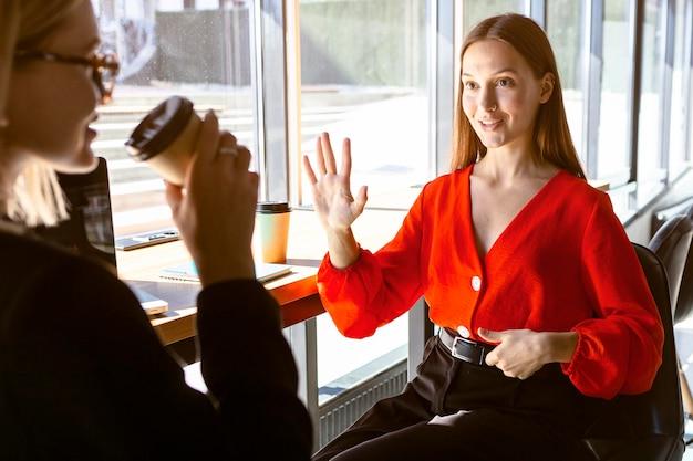 Zakenvrouwen die gebarentaal gebruiken terwijl ze koffie drinken op het werk Gratis Foto
