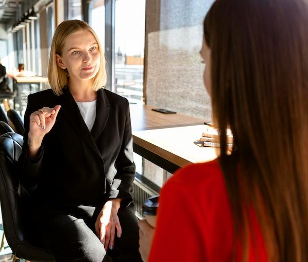 Zakenvrouwen die op het werk gebarentaal gebruiken om met elkaar te communiceren Gratis Foto