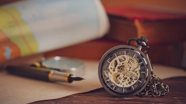 Zakhorloge met oude boeken en pen met papieren kaart op tafel bij het raam. Premium Foto