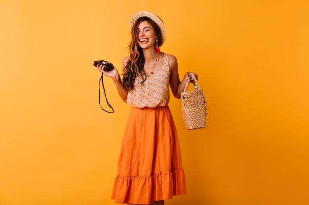 Zalige dame in trendy zomerkleren poseren met camera op geel. positieve mooi meisje in hoed koelen in de studio. Gratis Foto