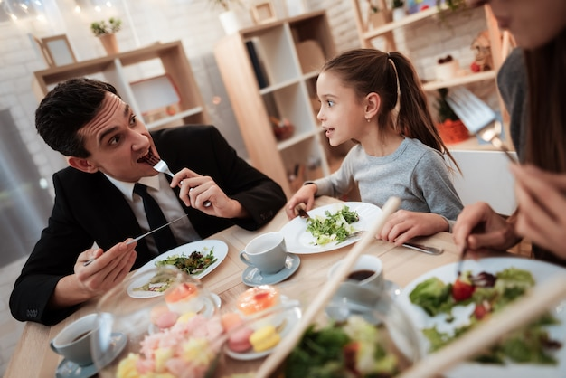Zalige familie die samen gerechten eet aan tafel. Premium Foto