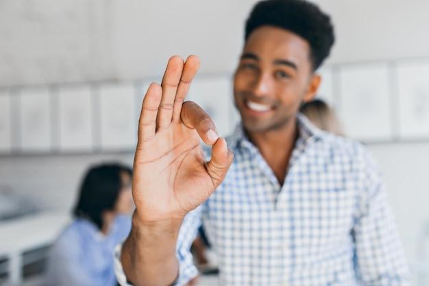 Zalige kantoormedewerker die plezier heeft met collega's en goed teken toont. indoor portret van lachende zwarte jonge man aan het werk in internationaal bedrijf met zijn hand in focus. Gratis Foto