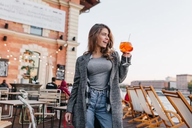Zalige vrouw in casual kleding die glas met oranje cocktail opheft op stadsachtergrond Gratis Foto