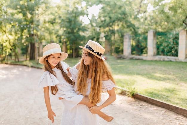 Zalige vrouw met lang blond haar met blootsvoets meisje in trendy schipper met de natuur. outdoor portret van vrolijke jonge moeder tijd doorbrengen met kind in zomerdag. Gratis Foto