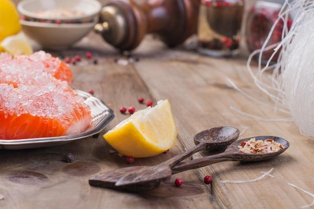 Zalm wordt gesneden en bestrooid met zout en kruiden, op een houten bord Premium Foto