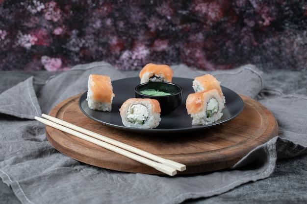 Zalmrolletjes in een zwarte schotel met wasabisaus. Gratis Foto