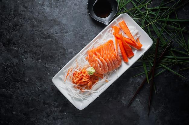 Zalmsashimi en imitatie krabstok in japanse stijl met kimchi, wasabi. Premium Foto
