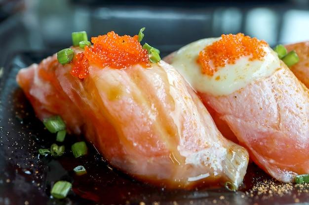 Zalmsushi met tobiko-eieren op bovenkant in zwarte plaat. Premium Foto