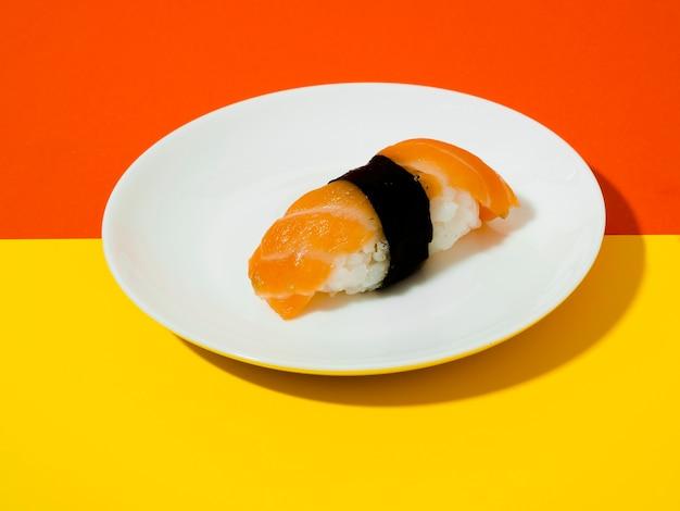 Zalmsushi op een witte plaat op een gele en oranje achtergrond Gratis Foto