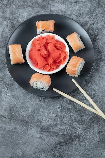 Zalmsushi rolt geserveerd met rode gember op een zwarte plaat. Gratis Foto