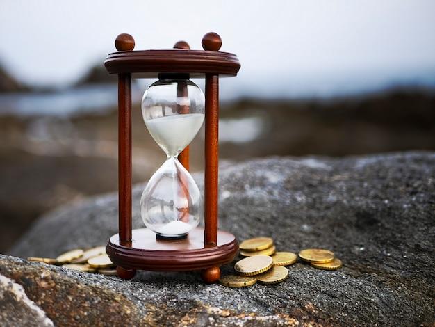Zand loopt door de vorm van zandloper met munten op rots achtergrond. tijdsinvestering en pensioensparen. Premium Foto
