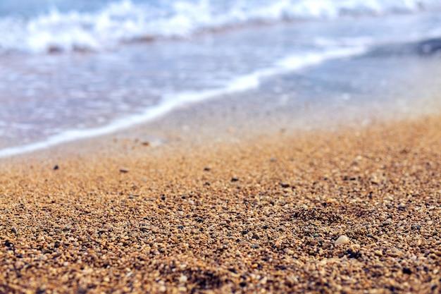 Zand op de oever van de zee. kleine kiezelsteen op het strand van turkije. zee achtergrond. kemer Premium Foto