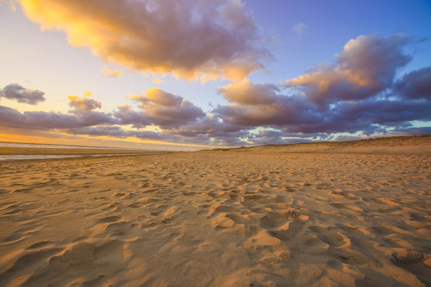 Zandduin op strand bij sunsetas voor aardachtergrond Premium Foto