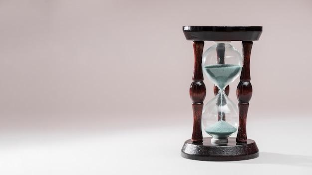 Zandloper als tijd voorbijgaand concept voor bedrijfsdeadline op gekleurde achtergrond Gratis Foto