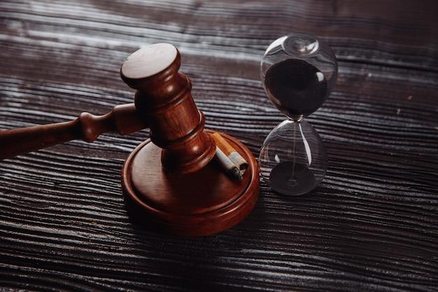 Zandloper en houten rechter hamer op een tafel Premium Foto