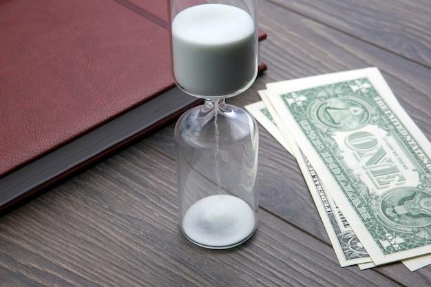 Zandloper, geld en notitieboekje liggen op tafel. zakelijke kantoorartikelen. tijd is geld. zakelijke oplossingen op tijd. Premium Foto