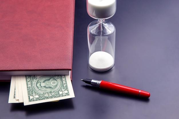 Zandloper, geld, pen en notitieboekje liggen op tafel. zakelijke kantoorartikelen. tijd is geld. zakelijke oplossingen op tijd. Premium Foto
