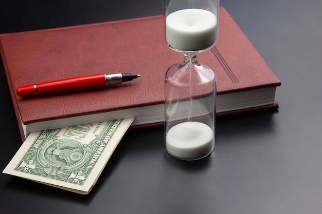 Zandloper, geld, pen en notitieboekje liggen op tafel. zakelijke kantoorartikelen Premium Foto